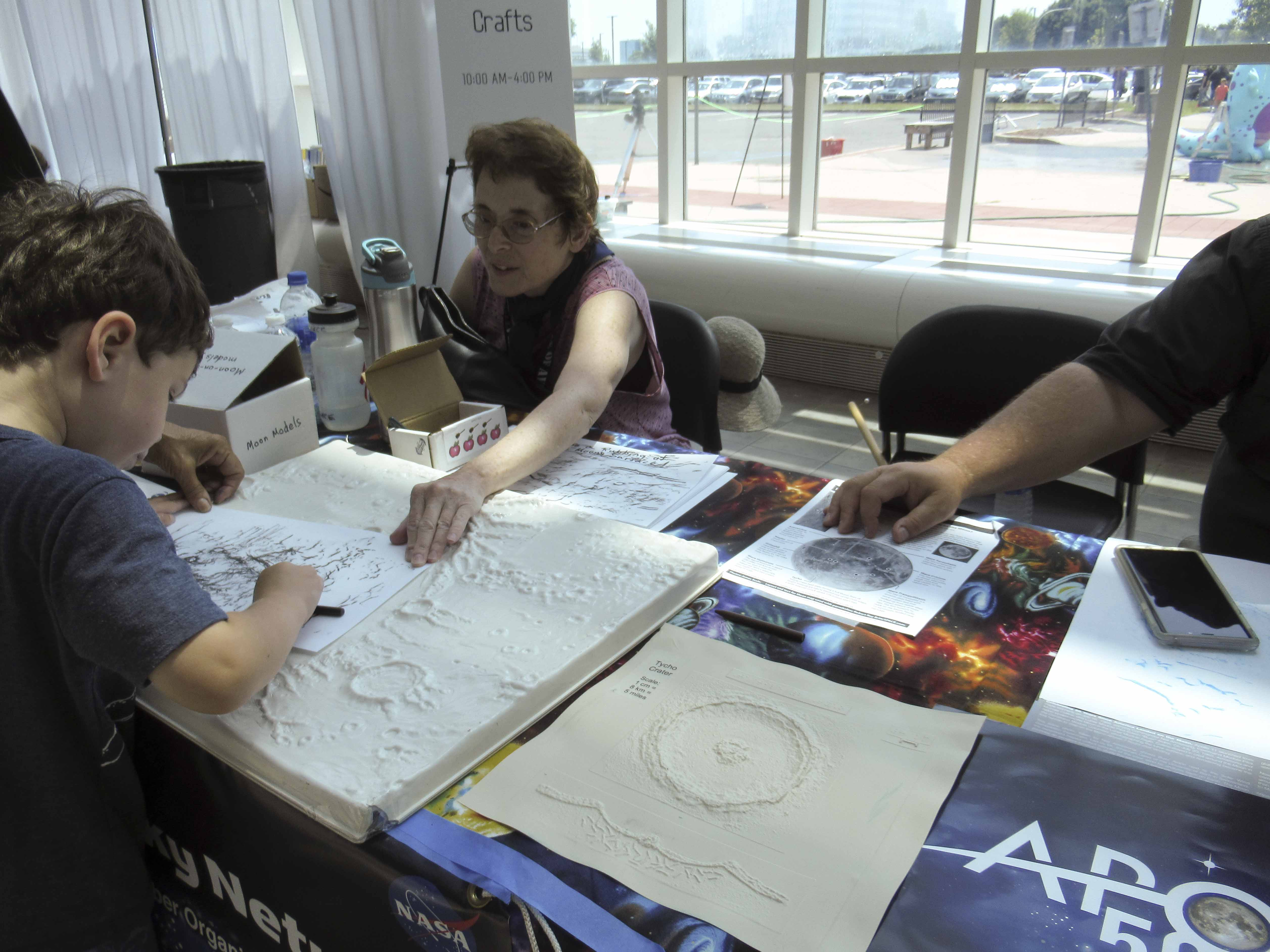people gather around a table to touch a tactile Moon display