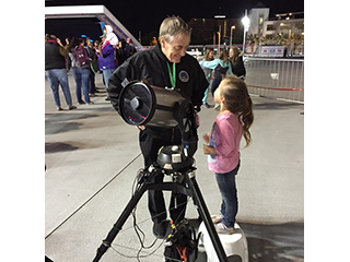 A girl and an astronomer smile at each other behind a telescope