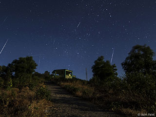 Photo of Perseid meteors streaking over a mountaintop